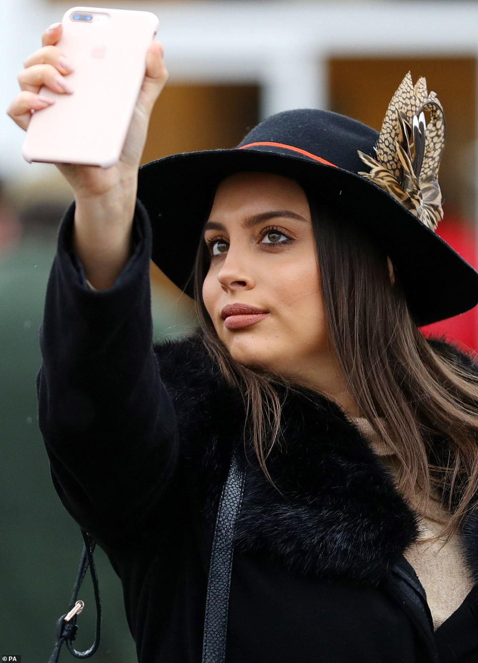 Selfie queen: A racegoer pauses to get a snap of her best side as she marches into the paddock for the final day of the meet