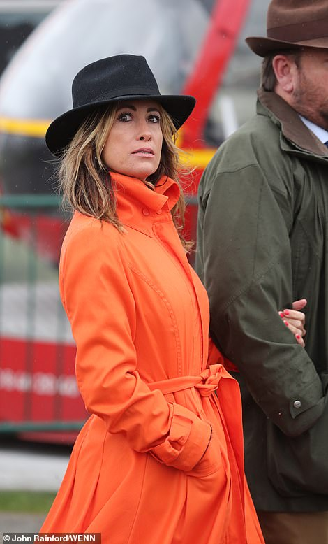 A reveller strides into the grounds in a bright orange mac
