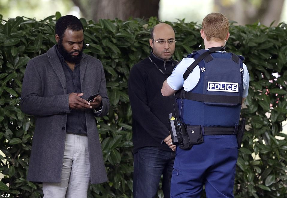 A police officer photographs witnesses near the scene of one of the shootings on Friday. The massacre happened during Friday prayers