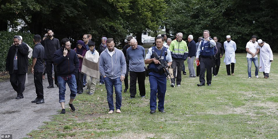 Police escort distraught witnesses away from a mosque in central Christchurch following the massacre. A 28-year-old man has been charged with murder