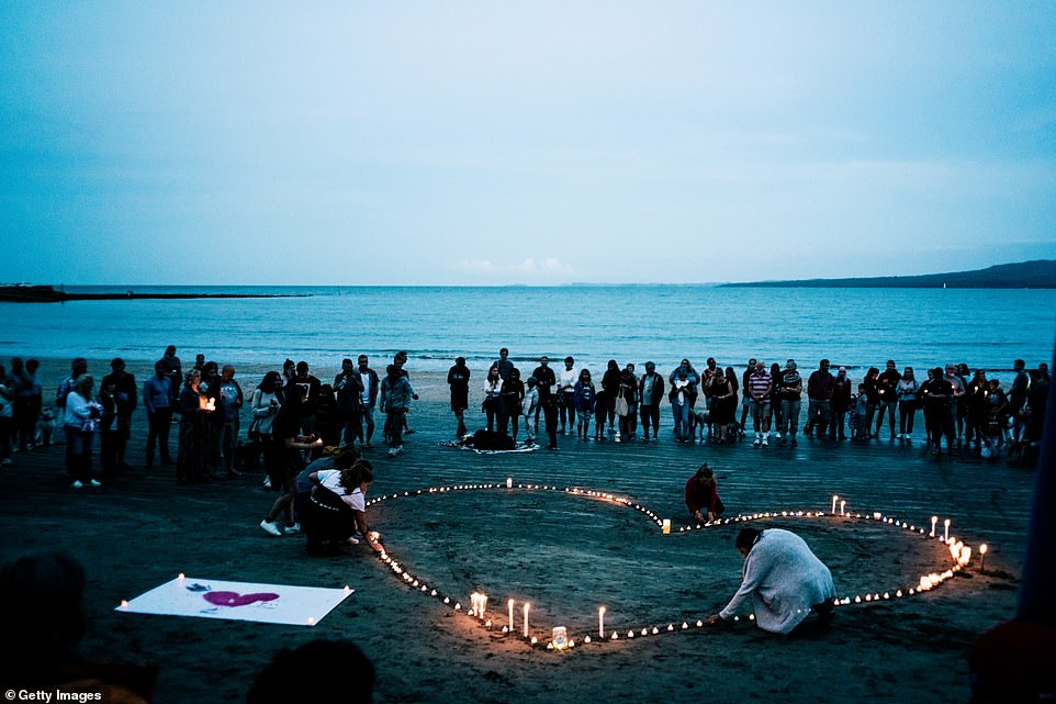 Crowds of mourners have gathered for a vigil in memory of the victims on Takapuna Beach in Auckland