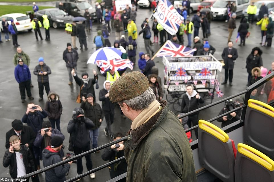Save our sovereignty: Supporters waved their flags and took photos of Mr Farage as he stood at the top of his 'Leave means Leave' bus