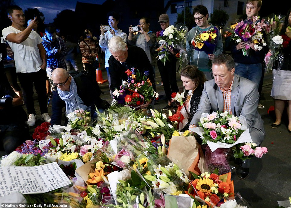 Members of the community move flowers closer to one of the mosques as part of a vigil after the attack yesterday