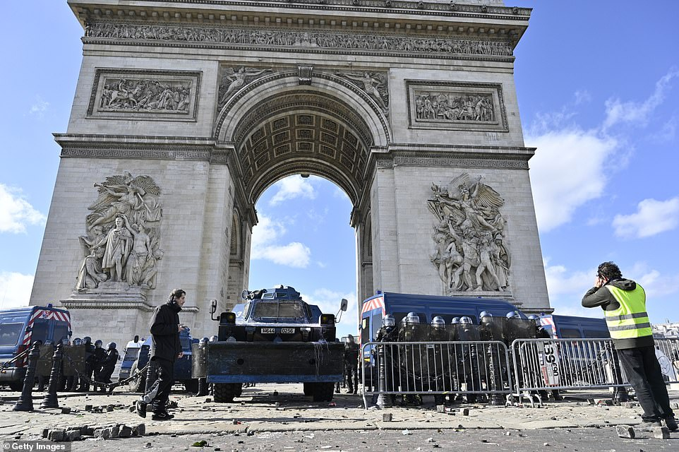 Security forces stand guard as yellow vests protesters stage a demonstration on avenue Champs Elysees in Paris, France