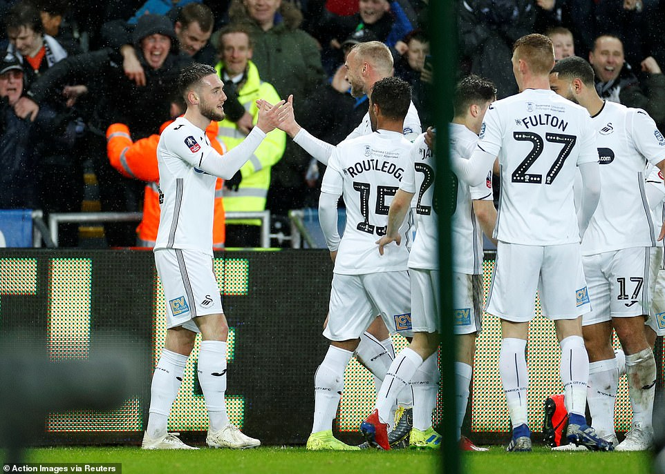 Grimes is congratulated by his jubilant Swansea team-mates after he gave Swansea a surprise lead