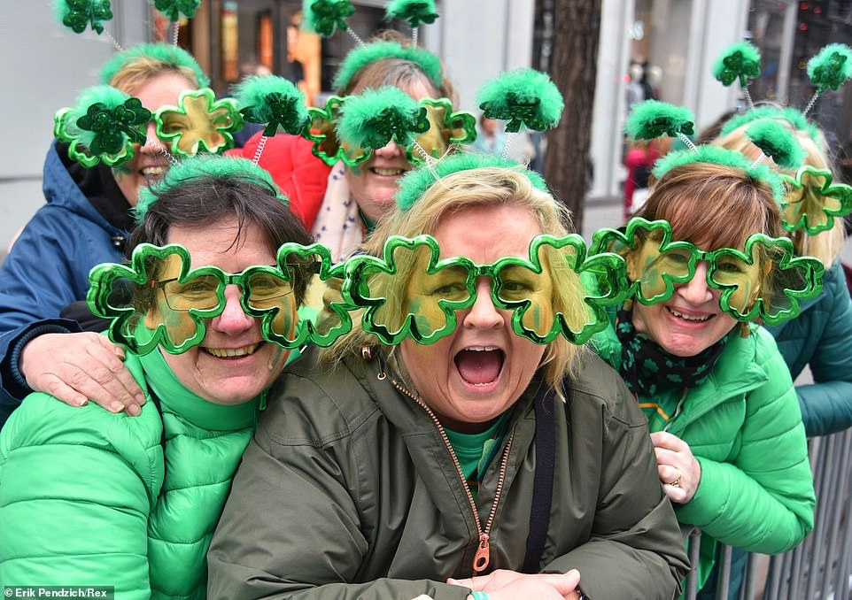 Women wear clover glasses as he she watches the 258th St Patrick's Day Parade on 5th Avenue in Manhattan in New York