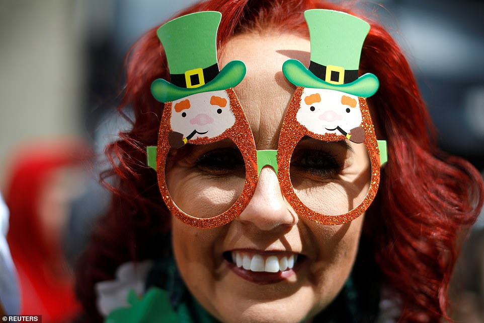 A redhead woman wears novelty glasses as he she watches the 258th St Patrick's Day Parade on 5th Avenue in Manhattan