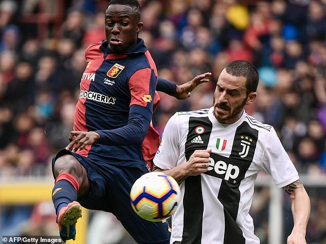 Genoa's Cristian Kouame competes for the ball with Juventus defender Leonardo Bonucci