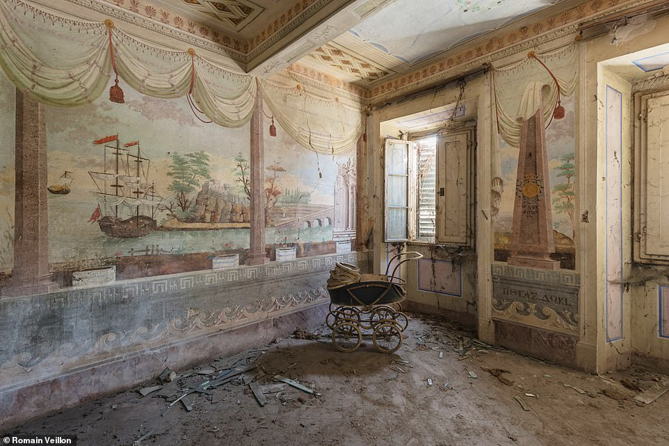 An abandoned pram lies rotting next to a wall adorned with the painting of a ship and a desert island in an empty mansion