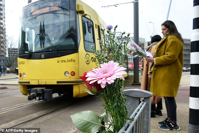 Respects: Many people could be seen carrying flowers to 24 Oktoberplein square in central Utrecht yesterday to pay tribute to the victims of Monday's shooting