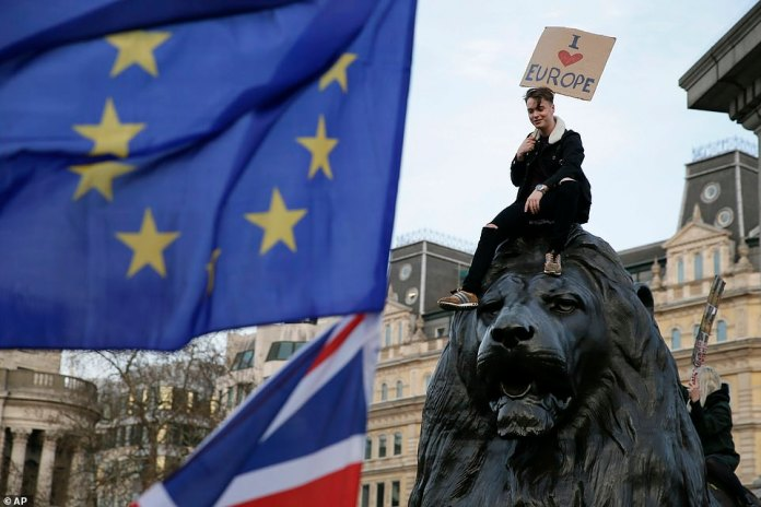 A demonstrator sits on one of the lions in Trafalgar Square during the march. The young man holds an 'I love Europe' sign