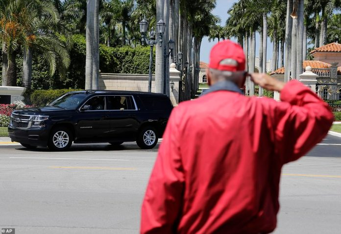 A trailer greets as the motorcade with President Donald Trump leaves the Trump International Golf Club on Saturday