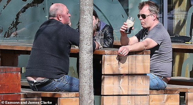 In good company: Gregson was joined by friends while occupying an outdoor table, where he downed a Guinness and smoked a cigarette