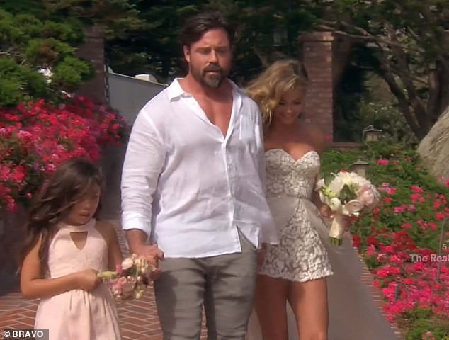 Family first: Aaron held hands with Denise and her seven-year-old daughter Eloise as they walked down the aisle together