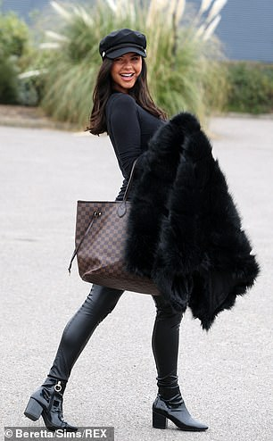 Stylish: The tanned beauty, 26, looked sensational in skintight black leather leggings and patent sock boots