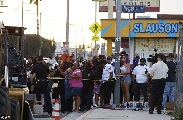 People gathered across the street of the Marathon Clothing store on Sunday after reports of the shooting first broke