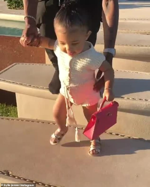 Stylish: Stormi looked cute in a white knitted outfit that had a drawstring waistband with pom poms and buttons.  The little girl also wore gold sandals and had her hair styled into a high ponytail