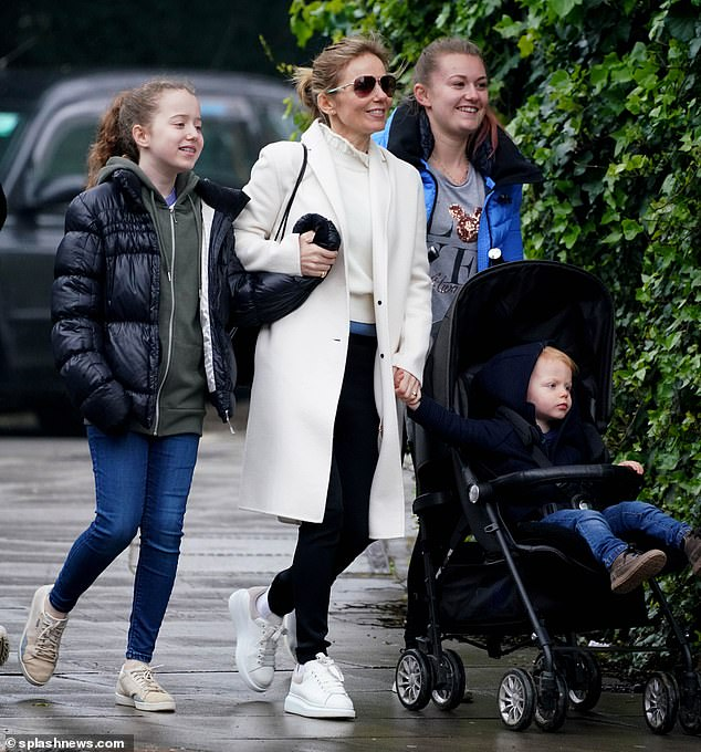 Smile: every inch the family unit, Geri clung to Monty's hand as the group walked forward, before picking up a bouquet of flowers