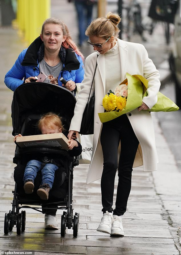 doting; Geri watched his son adoringly as he was being pushed by a friend