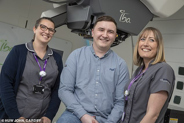 Mr Scott, pictured with staff at the centre, was getting ready to travel to the US for proton beam therapy for a brain tumour before being told he could have it in his home of Wales