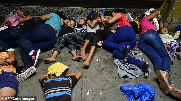 Children and their parents huddled together and slept in the streets as they awaited more shuttles from the center