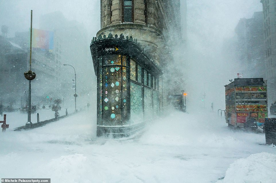 Manhattan's iconic Flatiron Building is captured while being whipped by icy winds during a snowy winter blizzard