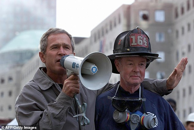 Moment of history: George W Bush held on to Bob Beckwith, a retired FDNY firefighter who had come to Ground Zero to help what was by then a search for human remains. They were standing on top of rubble which was over a fire truck and Beckwith, then 69, and now 85, handed a bullhorn to the president, who waved aside the Secret Service and told him to stay