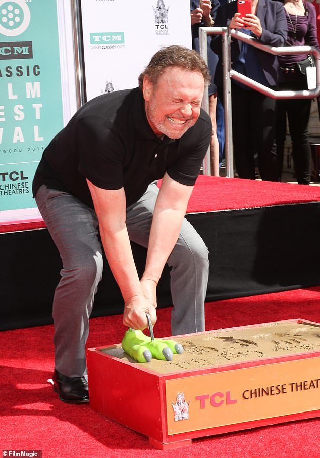 Mugging for the cameras: Billy made a big show of not being able to wrench the monster foot from the cement once it had made its mark