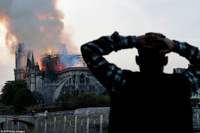 A man holds his hands on his head in despair as the smoke billows from the cathedral this evening as firefighers desperately battle the blaze