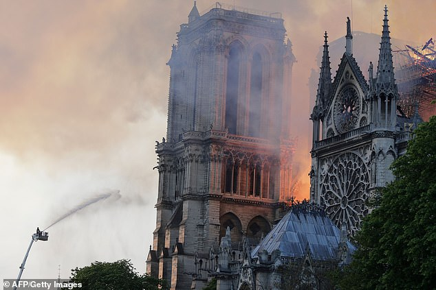 Jets of water are seen desperately trying to extinguish the flames engulfing Notre Dame