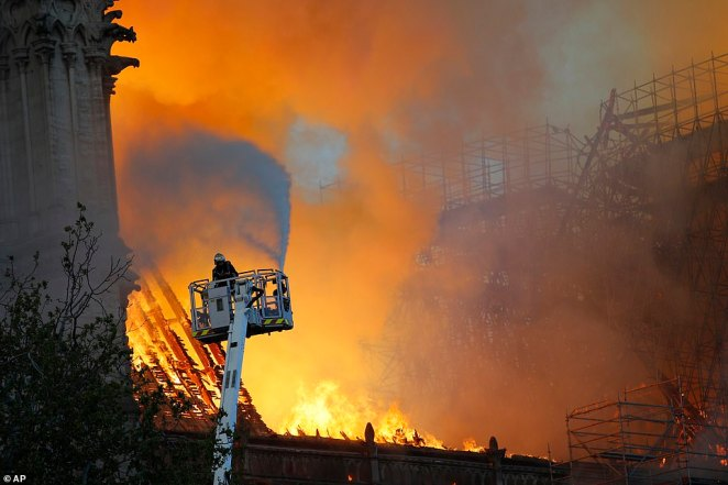 A lone firefighter on a crane uses a hose to try and extiguish the flames this evening. British Prime Minister Theresa May expressed her thoughts for the people of France and emergency services battling a devastating fire this evening