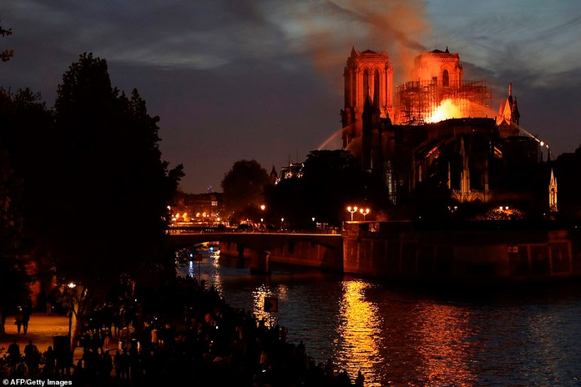 As darkness fell on Paris on Monday evening the ruined cathedral was illuminated by the flames still burning in the roof as firefighters battled on against the inferno