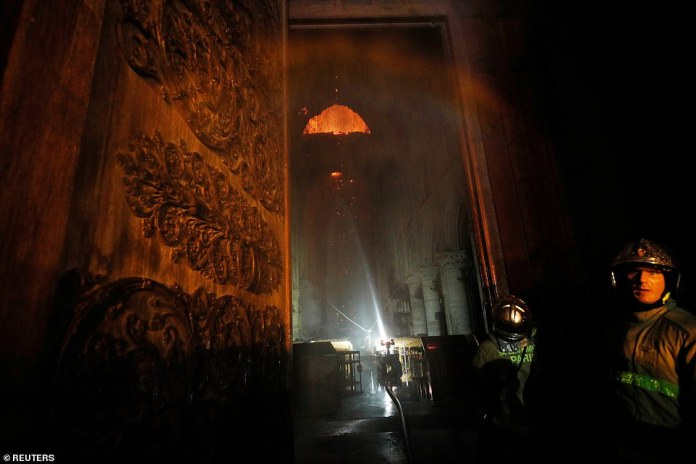 A view from inside the cathedral shows flames in the roof as firefighters douse it from below with hoses. A shocked firefighter looks back at the camera as the bright burnt orange blaze can be seen raging in Paris on Monday evening