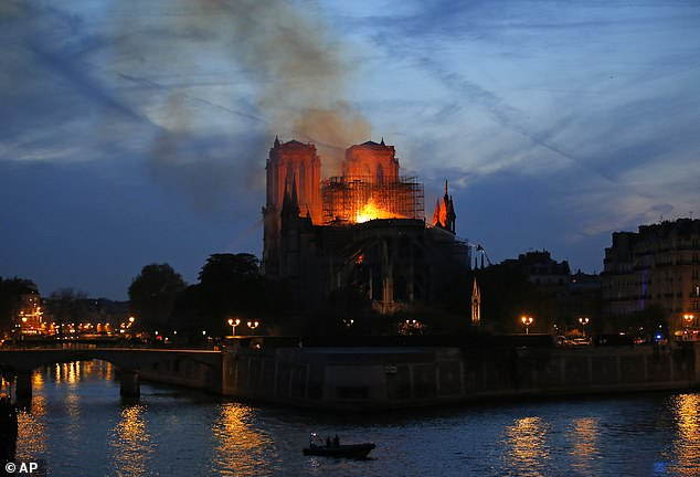 Firefighters tackle the blaze on Monday evening as flames and smoke rise from the Notre Dame cathedral as it burns in Paris