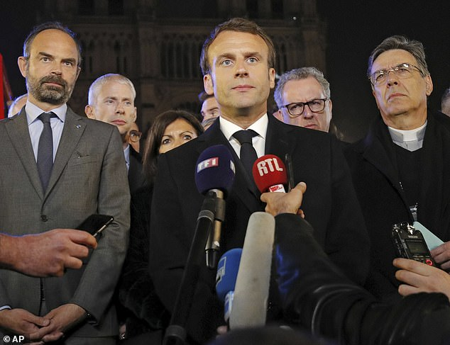 French Prime Minister Edouard Philippe, left, French President Emmanuel Macron, and Archbishop of Paris, Michel Aupetit, right, answer reporters after watching the fire at Notre Dame Cathedral