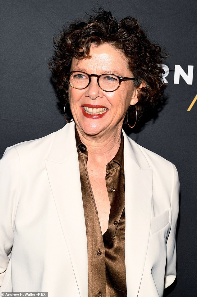All smiles: The 60 year old Bening was wearing an off-white pantsuit with a metallic brown dress shirt underneath