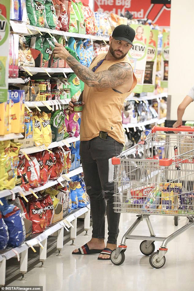 He also wore a stylish pair of slides and accessorised with a black cap while picking up At one point, Dan was seen shopping in the potato crisps aisle before picking up a packet of Doritos.
