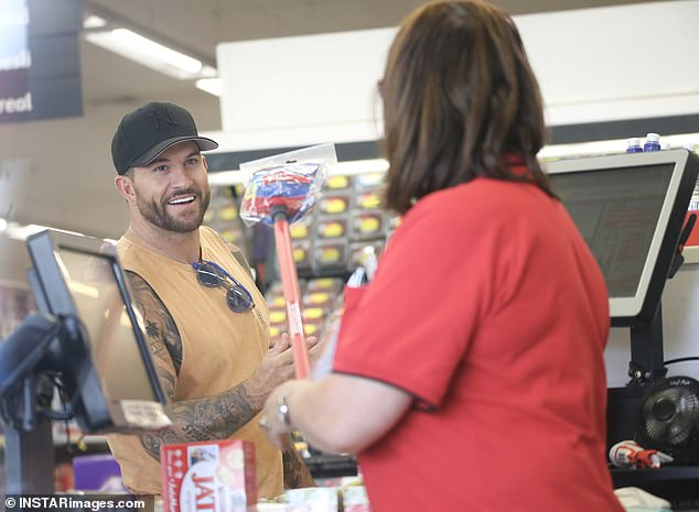 Happy chap: Dan flashed his pearly whites during a friendly chat with this Coles employee