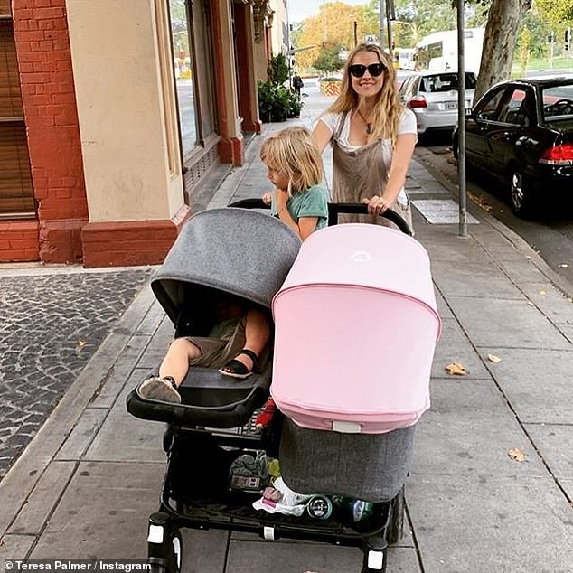 'First city stroll!' Teresa Palmer (pictured), 33, headed out with her growing brood to get newborn baby Poet's birth certificate on Wednesday. She was joined by husband Mark Webber and the couple's other two children, Bodhi Rain (middle), 5, and Forest Sage, 2, on the outing