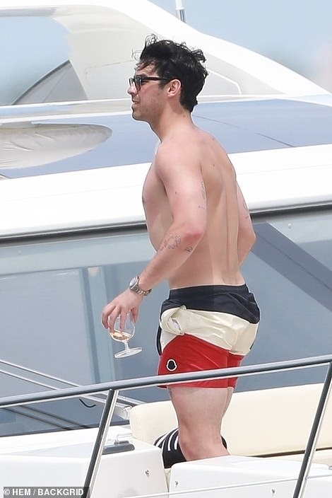 Time off: The singer enjoyed a drink in the sunshine aboard the luxuy yacht