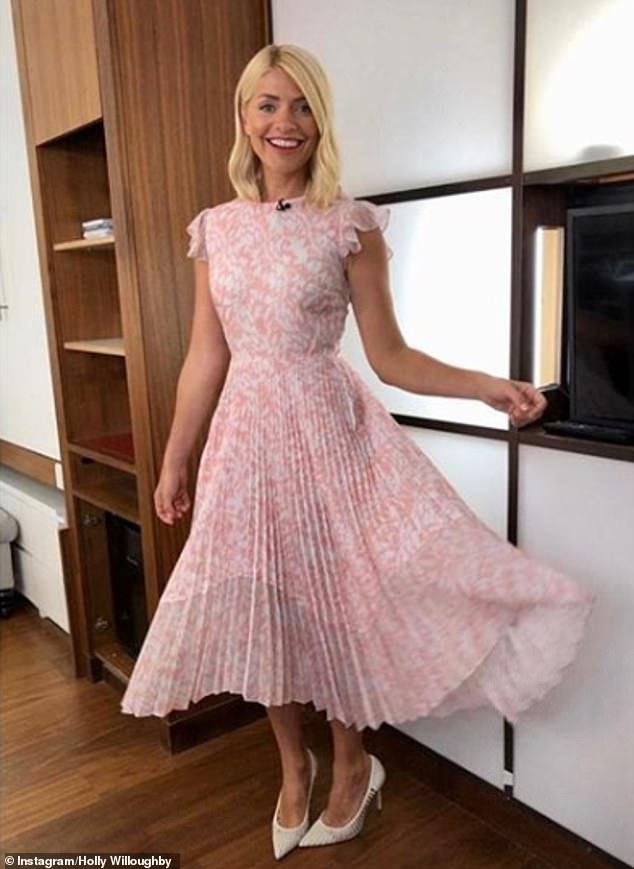 Días felices: la presentadora de televisión mantuvo su estilo glamoroso mientras compartía un hermoso broche de oro desde su primer día en el trabajo, luciendo un vestido midi rosa claro plisado de Markus Lupfer