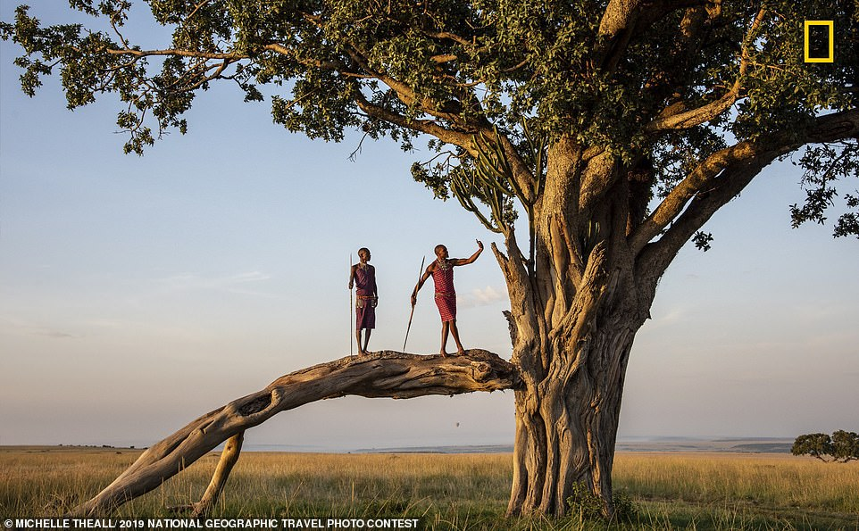 Describing this shot, taken in Kenya, photographer Michelle Theall said: 'On safari in the Mara, these Maasai men were going to perform a morning dance for us, but before they did, I saw this man taking a selfie with his smartphone. It seems technology invades every space of our world'