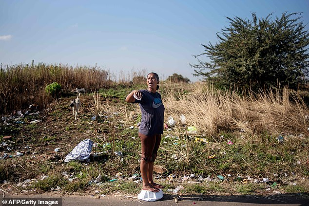 Community member Nicole Ricketts, 19, gestures to catch the attention of others in Eldorado Park as they prepare a clearing in a plot of land during a land grabbing action