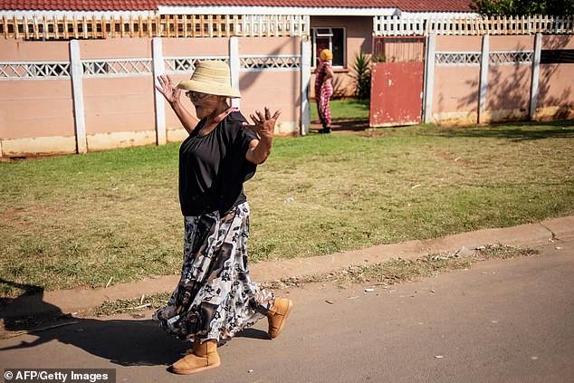 A woman walks along the street of Eldorado Park during a land grabbing action on the outskirts of Johannesburg on April 18