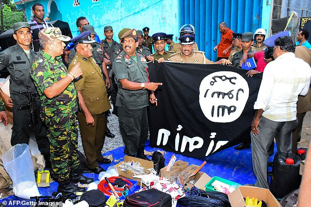 Army officers pose with an Islamist flag after their ferocious raid on the safe-house on Friday evening