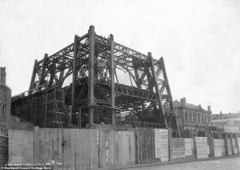 When the tower was first being built the site was cordoned off with just wooden fencing and a sign can be seen on the right hand side, comparing it to the Eiffel Tower