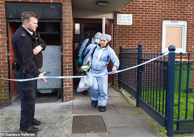 Forensics officers leave the flat in Canning Town, east London, while investigating on Monday