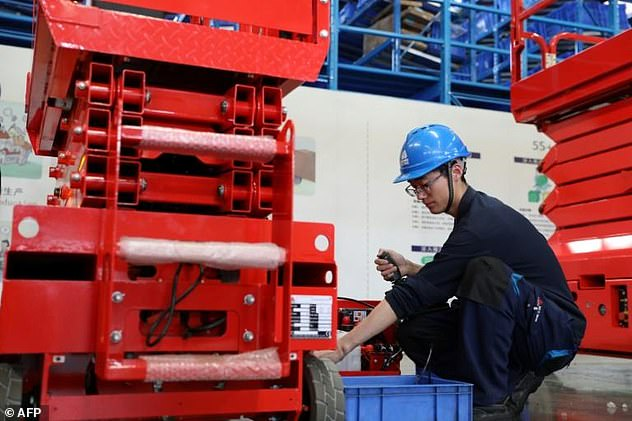 A Chinese worker adjusts a hydraulic lift at a factory which produces construction machinery for export to many countries, including the US, in Jinan, in east China's Shandong province