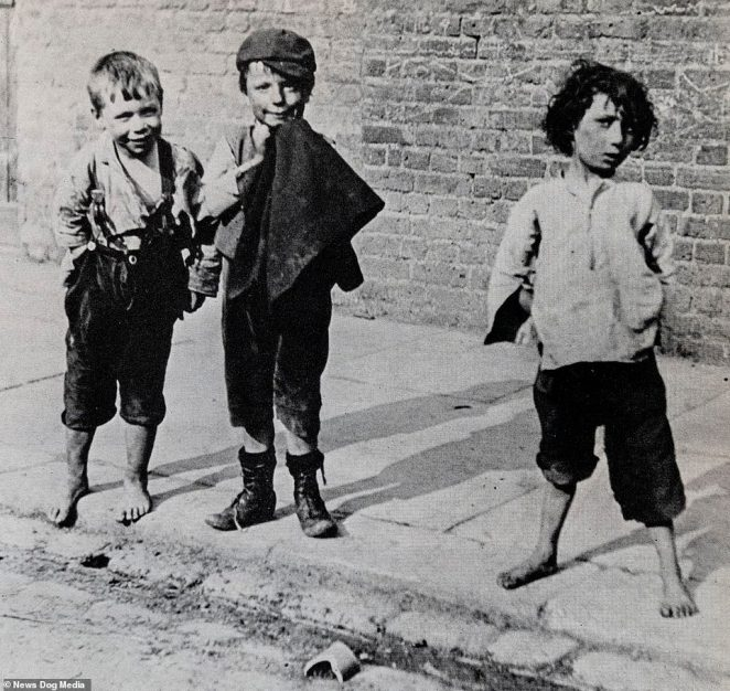 Three street children pose for the camera on a street in London in 1892. Mr Martin wrote: 'I called them human squirrels, for when they caught the sight of the school inspector, they were over a six-foot paling in a flash, and made off to Lambeth Walk'