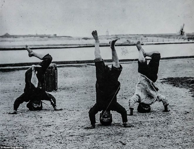 A further image taken by Victorian photographer Mr Martin shows three children larking around showing off for the photographer's camera in 1893 by doing head stands on a beach at an unknown location that appears to be outside London